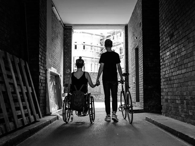 Mother in a wheelchair holding her son's hand
